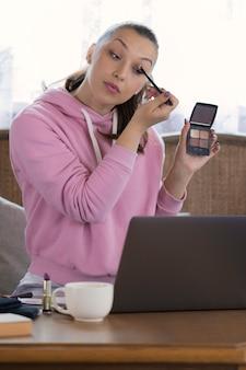Junge schöne frau aufnahme make-up-tutorial, um auf social media zu teilen, online-video-vlog mit make-up-kosmetik zu hause zu senden