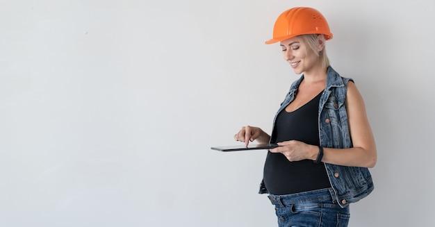 Junge schöne frau baumeister in einem orangefarbenen schutzhelm auf dem kopf. schwangeres mädchen. steht an der wand, hält ein tablet in der hand und tippt eine nachricht. hausrenovierungskonzept vor der geburt.