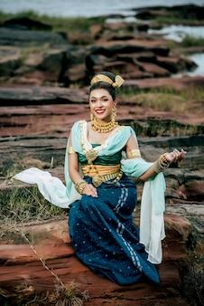 Junge schöne frau des porträts, die in der traditionellen tracht mit dem ornament trägt, das in der natur in thailand aufwirft?