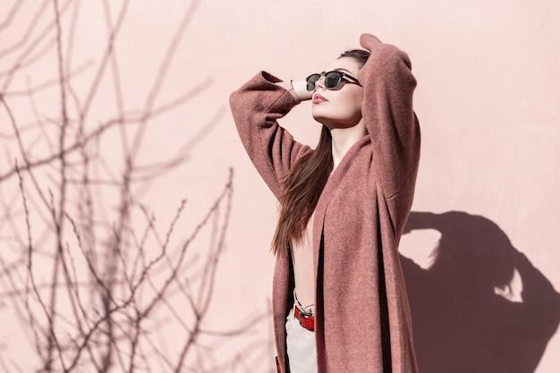 Junge schöne frau des porträts in der modischen sonnenbrille im stilvollen mantel mit den sexy lippen nahe der wand am sonnigen tag. schönes mädchen-mode-modell in stilvoller kleidung posiert und genießt frühlingssonnenlicht in der stadt.