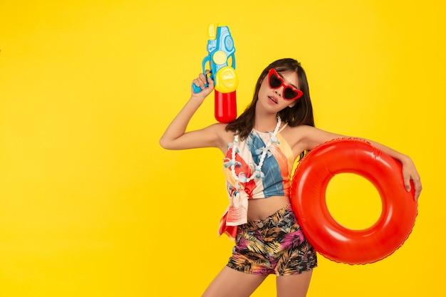Junge schöne frau des sommers mit wasserpistole und gummiband, songkran-feiertage
