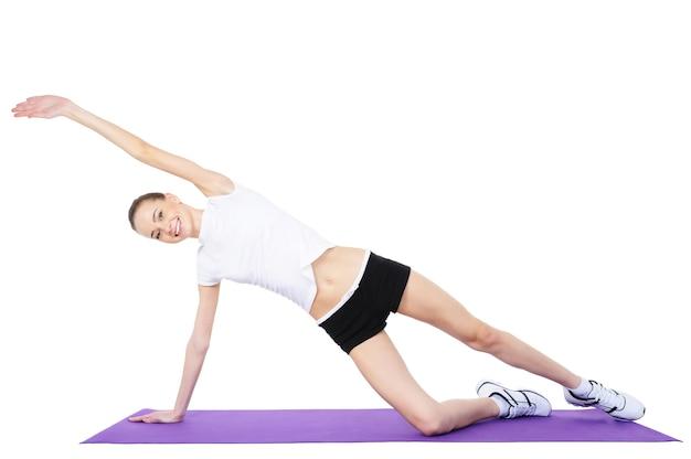 Junge schöne frau, die aerobic-übungen macht - lokalisiert auf weiß