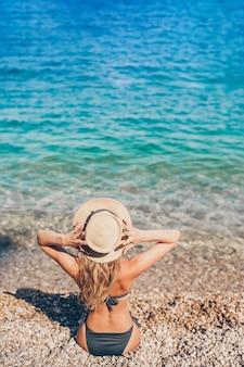 Junge schöne frau, die am europäischen strand sich entspannt