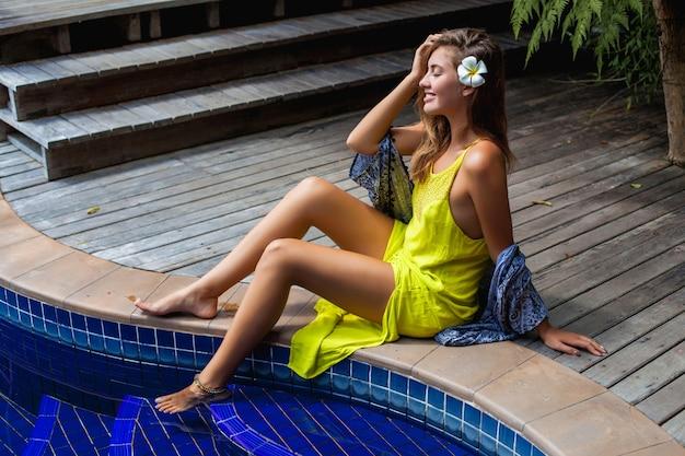Junge schöne frau, die am pool im gelben boho-kleid sitzt, sommertrendmode, sexy, dünne, gebräunte haut, schlanke beine, tropischer urlaub, resorthotel, lächelnd, sinnlich, reisen in asien, heiß,