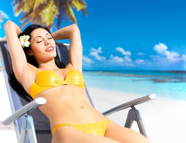 Junge schöne frau, die am strand sitzt auf stuhl genießt Kostenlose Fotos