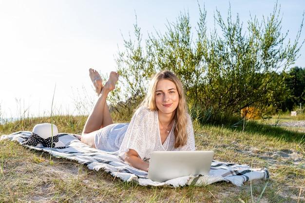 Junge schöne frau, die am strand sonnenbad und am computer arbeitet