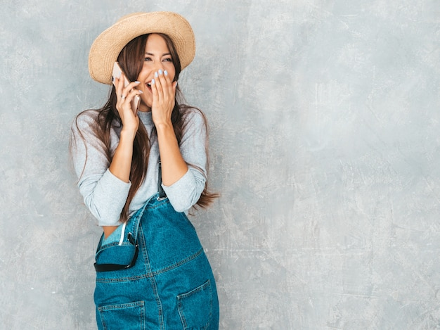 Junge schöne frau, die am telefon spricht. modisches entsetztes mädchen in der zufälligen sommeroverallkleidung und -hut. lustig und überrascht. schließt den mund