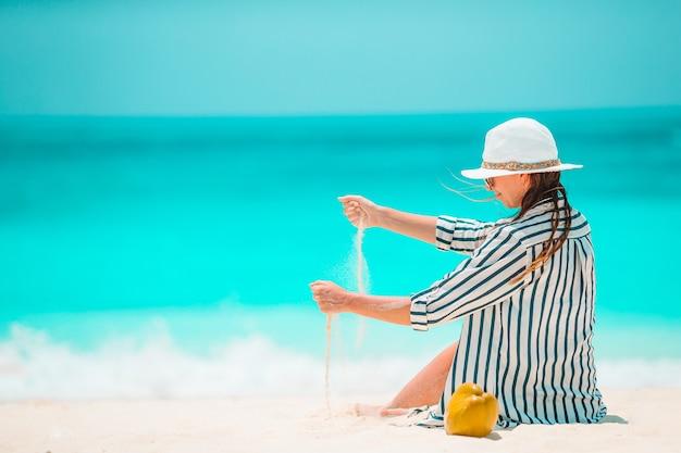 Junge schöne frau, die am tropischen strand des weißen sandes entspannt und mit sand spielt
