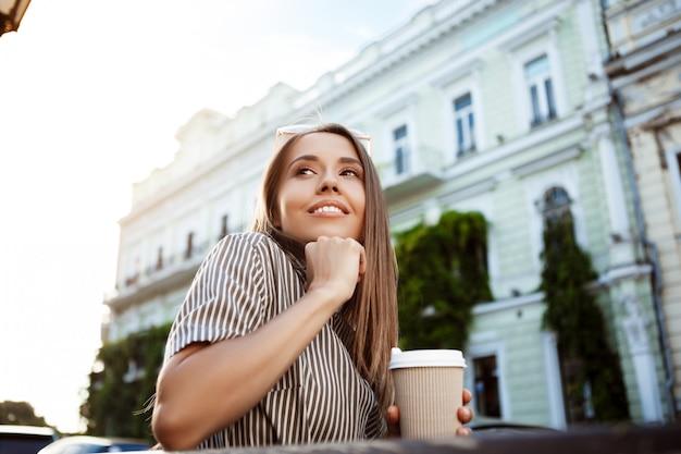 Junge schöne frau, die auf bank sitzt und kaffee hält