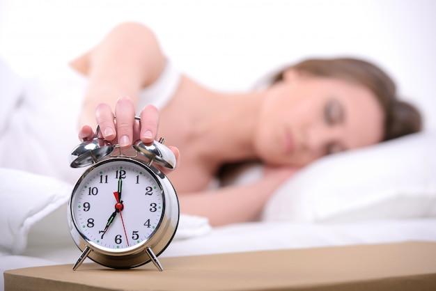 Junge schöne frau, die auf bett mit alarmuhr schläft.