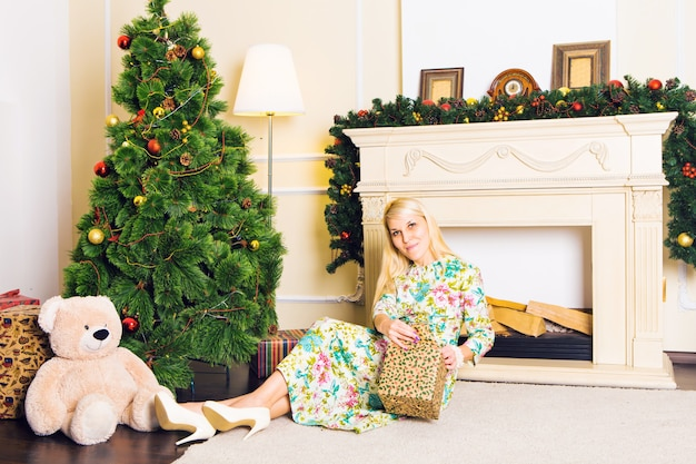 Junge schöne frau, die auf boden nahe weihnachtsbaum sitzt und an einem silvester präsentiert. innenraum mit weihnachtsdekorationen.
