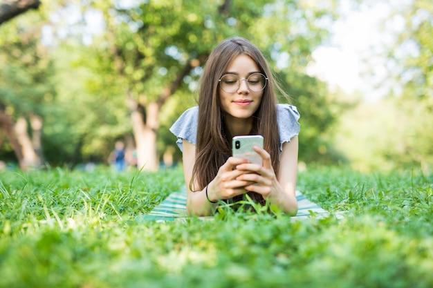 Junge schöne frau, die auf dem gras liegt, das eine nachricht auf einem handy im park liest