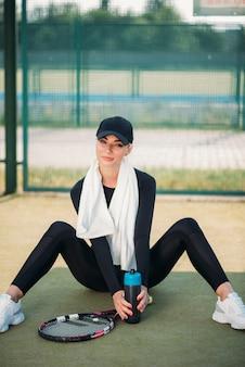 Junge schöne frau, die auf dem tennisgericht stillsteht. gesunder sportlebensstil
