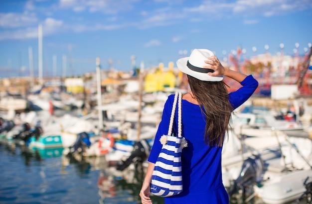 Junge schöne frau, die auf dock nahe dem boot am sonnigen tag sich entspannt