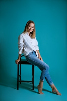 Junge schöne frau, die auf einem stuhl in einem weißen hemd und in jeans auf einer blauen wand barfuß aufwirft