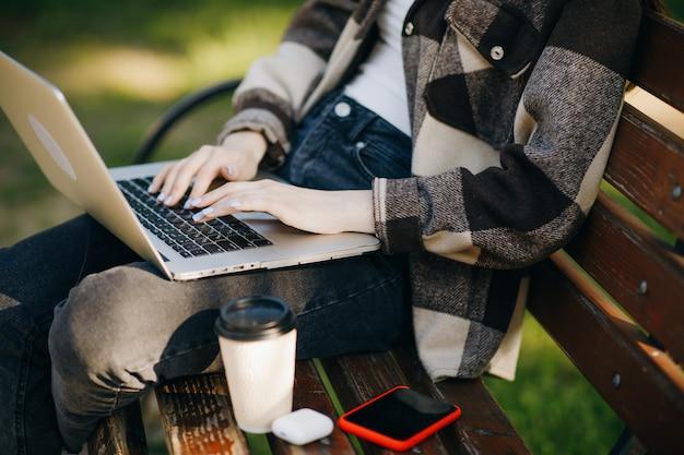 Junge schöne frau, die auf einer bank mit dem laptop steht