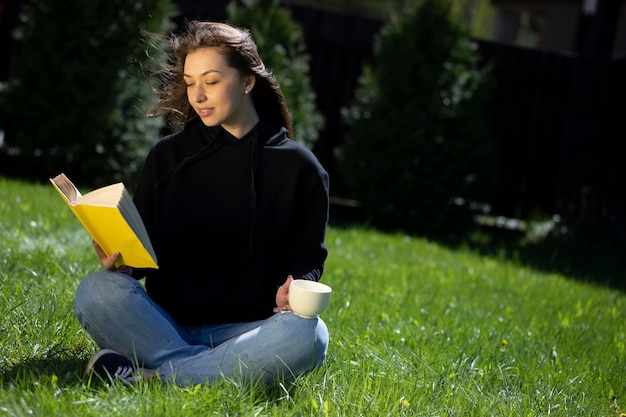 Junge schöne frau, die auf gras im park mit papierbuch und tasse tee sitzt, die ruht