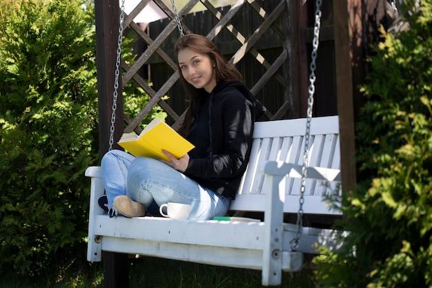 Junge schöne frau, die auf hölzerner schaukel im hinterhof des landhauses sitzt und buch draußen liest