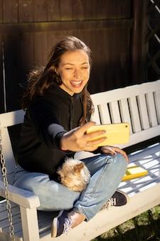 Junge schöne frau, die auf hölzerner schaukel mit kleinem hundehaustier sitzt und selfie macht