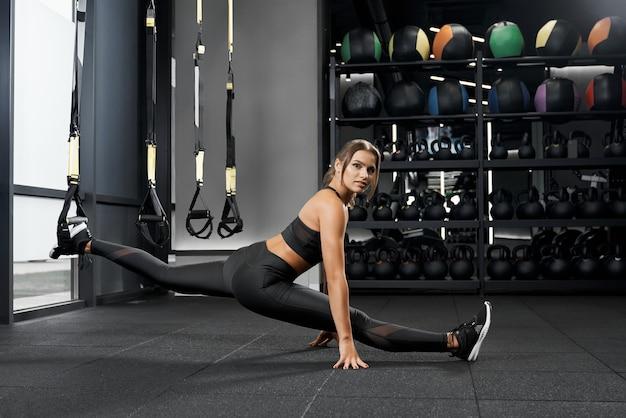 Junge schöne frau, die auf schnur im modernen fitnessstudio sitzt