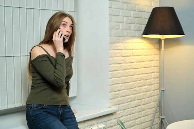 Junge schöne frau, die auf smartphone spricht, mädchen im hauptinnenraum, kopienraum
