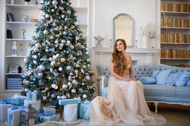 Junge schöne frau, die auf sofa nahe weihnachtsbaum sitzt