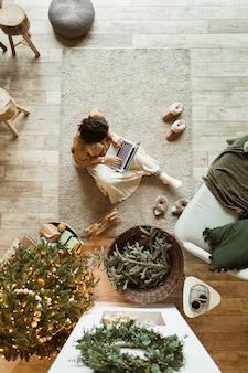 Junge schöne frau, die auf teppich sitzt und am laptop im gemütlichen bequemen wohnzimmer arbeitet, das für weihnachten verziert wird
