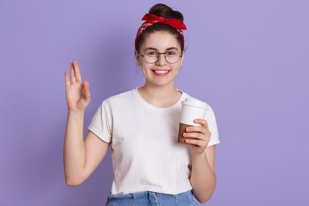 Junge schöne frau, die cu des kaffees wegnimmt, der über fliederraum isoliert wird, der ok zeichen mit den fingern tut, zeigt ausgezeichnetes symbol