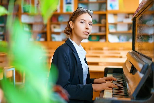 Junge schöne frau, die das klavier in der klasse spielt