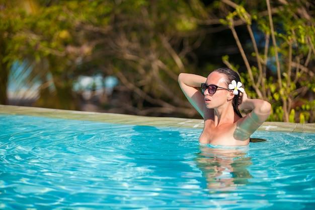 Junge schöne frau, die das ruhige luxuxschwimmbad genießt