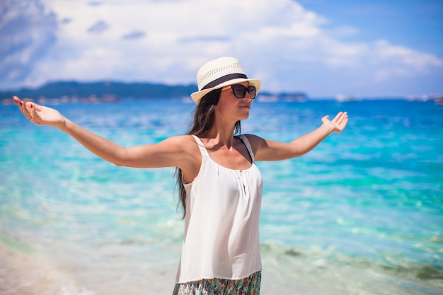 Junge schöne frau, die den feiertag auf weißem tropischem strand genießt