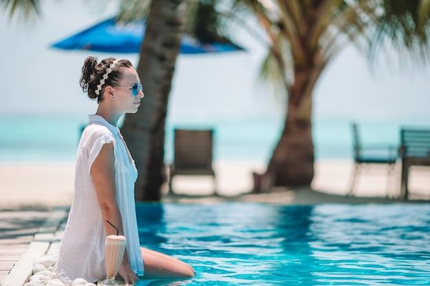 Junge schöne frau, die den luxuriösen ruhigen swimmingpool genießt