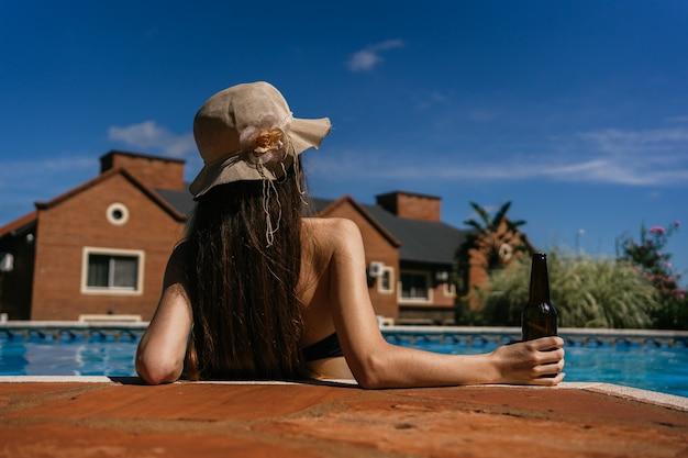 Junge schöne frau, die durch den pool entspannt
