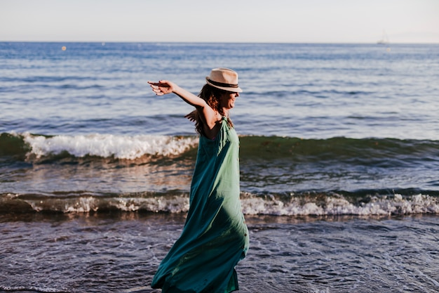 Junge schöne frau, die durch den strand am sonnenuntergang geht