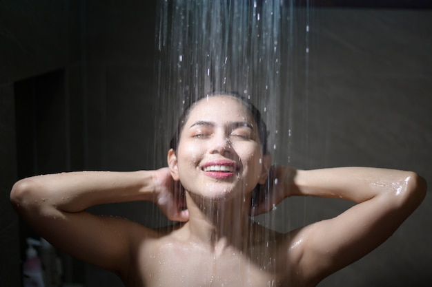 Junge schöne frau, die dusche in einem badezimmer zu hause nimmt