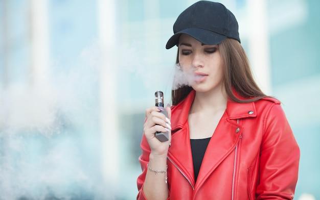 Junge schöne frau, die e-zigarette mit rauch raucht (vaping)