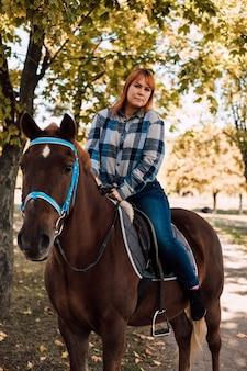Junge schöne frau, die ein pferd reitet