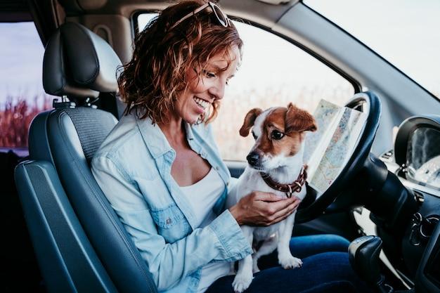 Junge schöne frau, die eine karte in einem auto liest. reisekonzept. süßer jack russel hund außerdem.