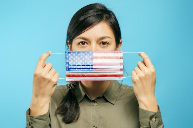 Junge schöne frau, die eine medizinische schutzmaske in ihren händen mit der amerikanischen nationalflagge auf einem blauen hintergrund hält