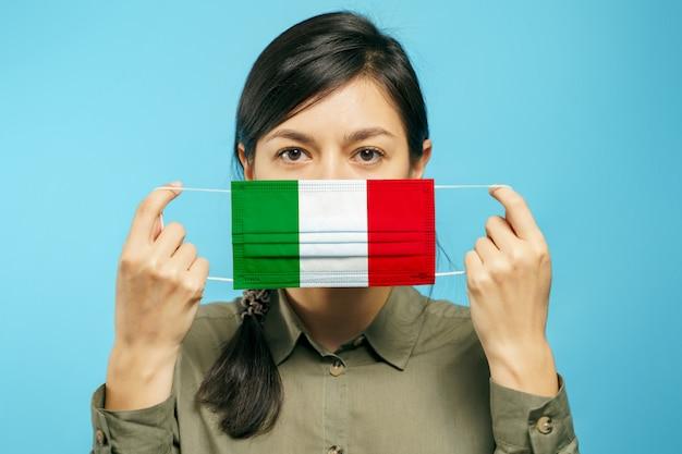 Junge schöne frau, die eine medizinische schutzmaske in ihren händen mit der italienischen nationalflagge auf einem blauen hintergrund hält
