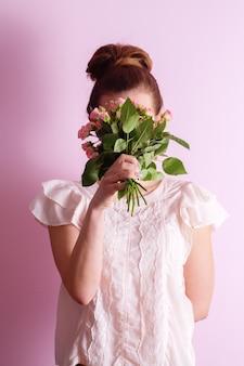 Junge schöne frau, die einen blumenstrauß der rosa rosen am valentinstag schnüffelt