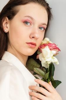 Junge schöne frau, die einen bündel roter rosen riecht. mode-innenfoto der schönen lächelnden frau mit dunklem haar, das einen großen strauß roter rosen am valentinstag hält