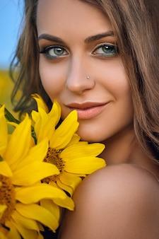 Junge schöne frau, die einen hut auf einem gebiet der sonnenblumen trägt