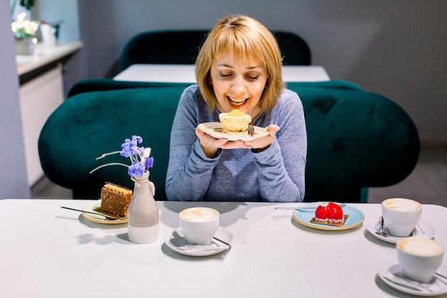 Junge schöne frau, die einen nachtisch mit guter zufriedenheit isst. frau, die am tisch im café sitzt. desserts, kaffee oder tee auf dem tisch, freunde treffen