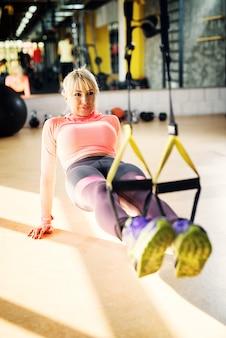 Junge schöne frau, die einige beinübungen in einem fitnessstudio mit trx macht.