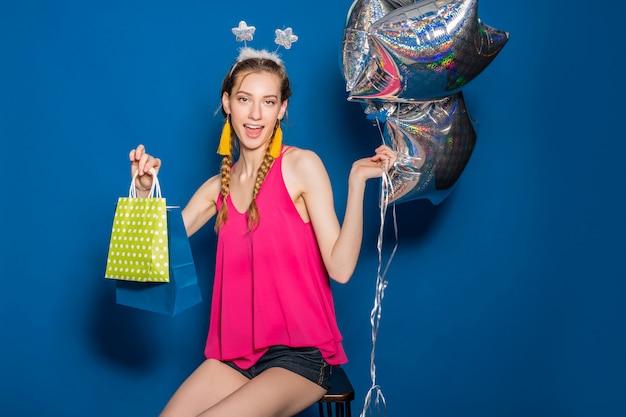 Junge schöne frau, die einkaufstaschen und luftballons hält