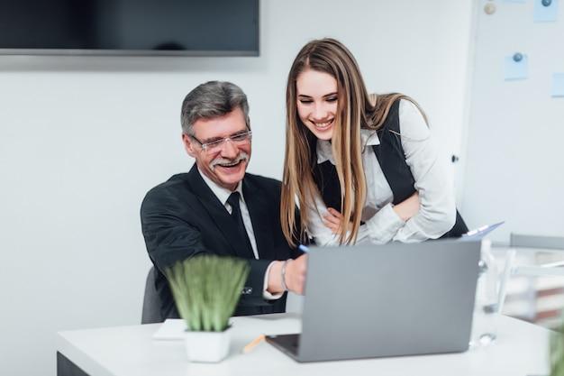 Junge schöne frau, die etwas bespricht und ihr digitales tablett ihrem kollegen zeigt, während sie am bürotisch sitzt. unternehmenskonzept.