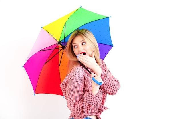 Junge schöne frau, die farbigen regenschirm auf weißem hintergrund hält