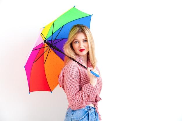 Junge schöne frau, die farbigen regenschirm auf weißer wand hält
