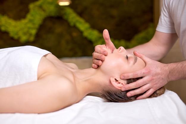 Junge schöne frau, die gesichtsmassage genießt männlicher therapeut, der kopf- und nackenmassage für die seitenansicht des weiblichen kunden macht
